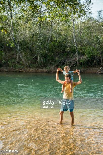 young man carrying son on his shoulders standing in river_ - mato grosso do sul state stock pictures, royalty-free photos & images