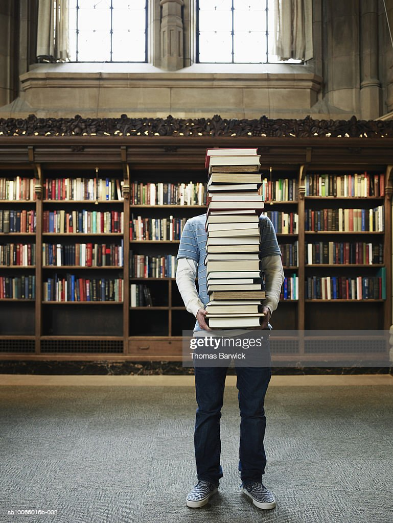Young man carrying stack of books in university library : Stock Photo