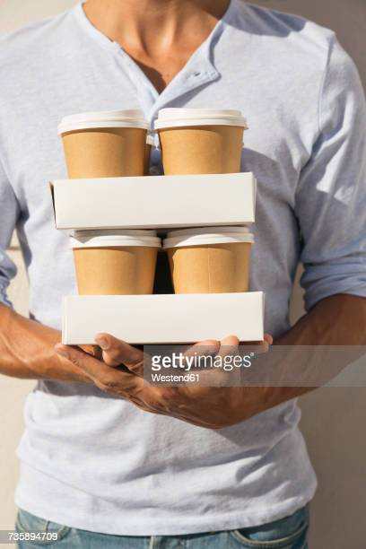 Young man carrying stacks of take away coffee