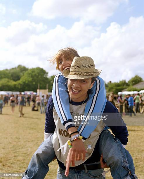 Young man carrying young woman on back, laughing, portrait