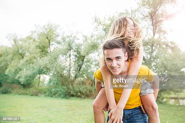 Young man carrying young woman on back, outdoors