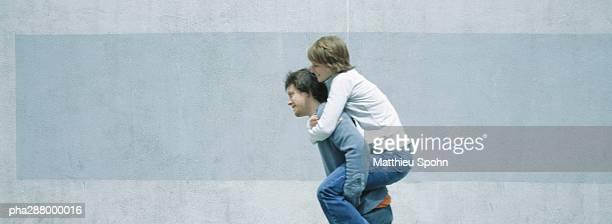 Young man carrying young woman piggyback