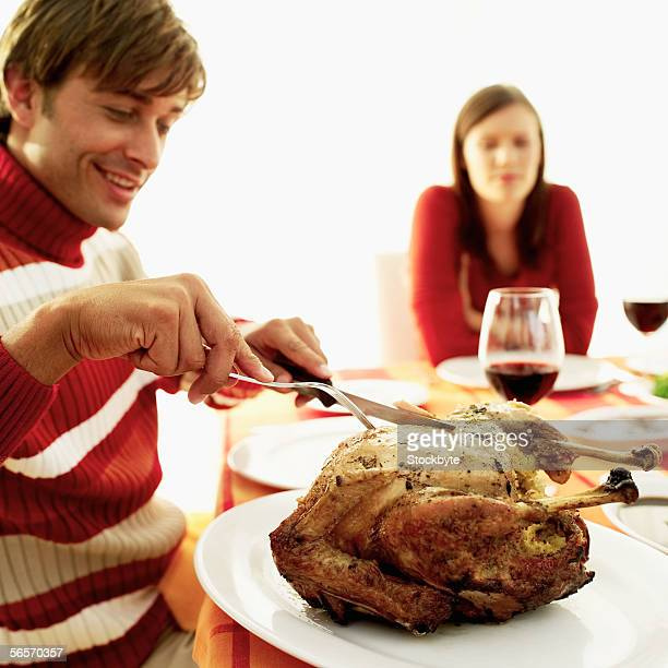 young man carving a roast turkey at the dinner table