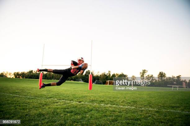 young man catching american football on field against sky - high school football stock pictures, royalty-free photos & images