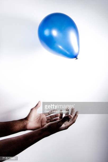Young man catching balloon, close-up