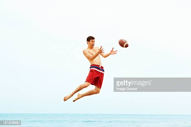 Young man catching rugby ball