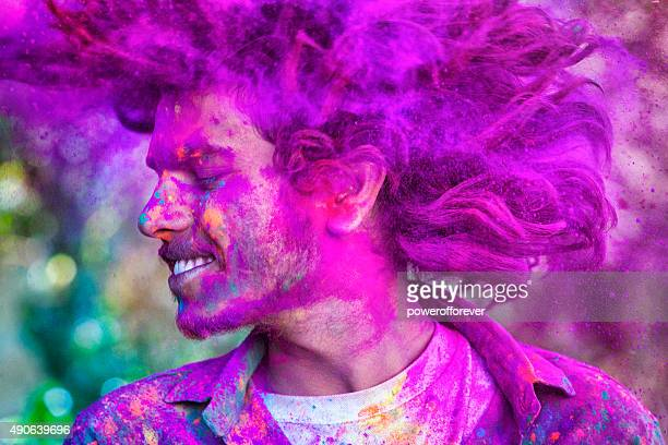 young man celebrating holi festival in india - holi stock pictures, royalty-free photos & images