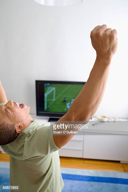 Young man celebrating in front of television