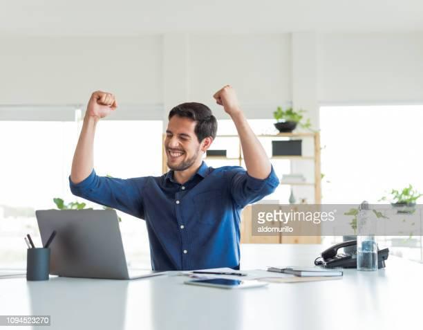 joven celebra en oficina - ganar fotografías e imágenes de stock