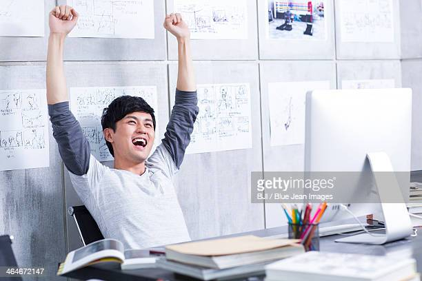 Young man celebrating in the office