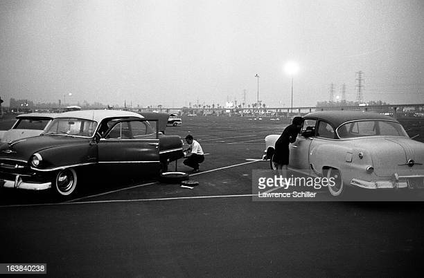 A young man changes a flat tire as a woman talks with another driver in the parking lot at the Disneyland theme park Anaheim California early 1960s...