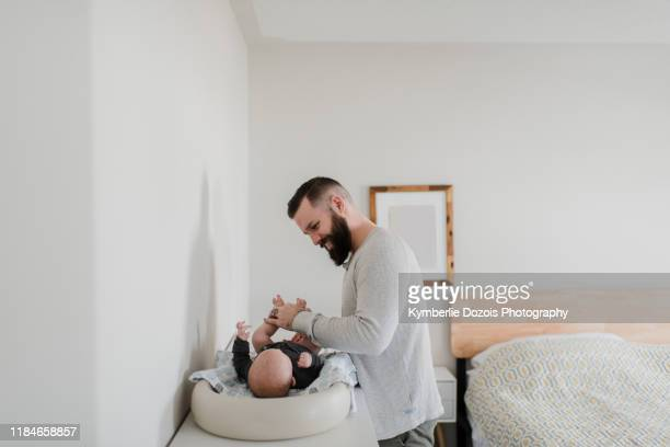 young man changing baby son's diaper in bedroom - オムツを替える ストックフォトと画像