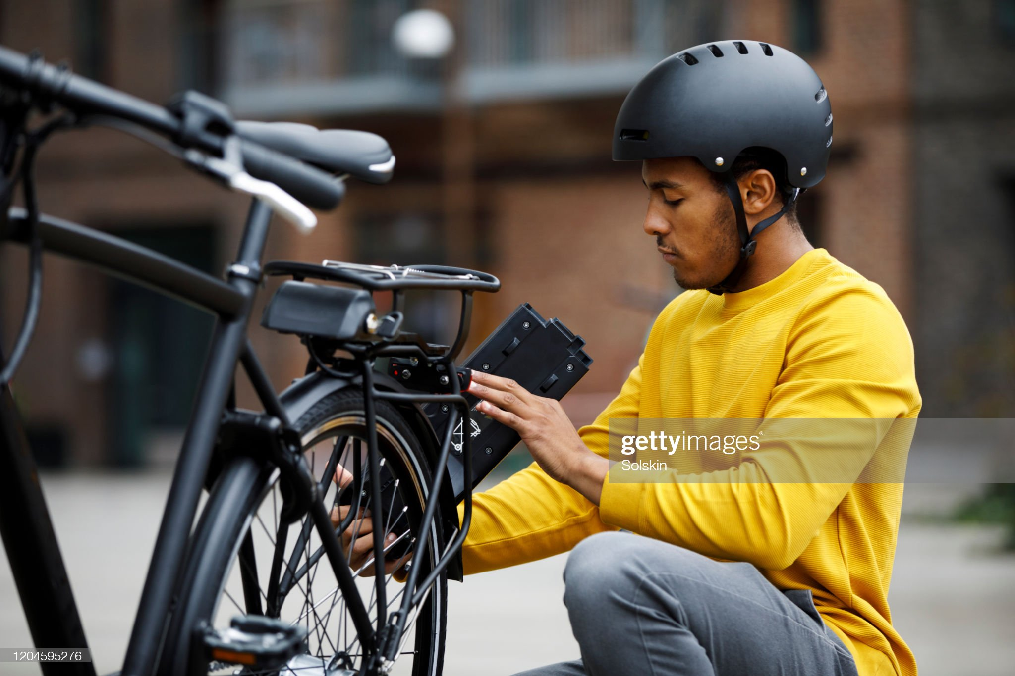 Young man changing battery pack on electric bicycle : Stock Photo