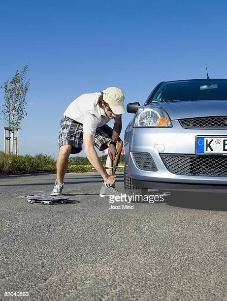 young man changing car wheel, outdoors