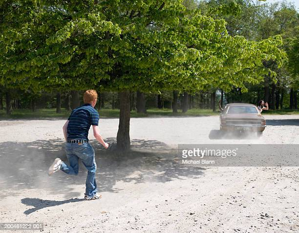 Young man chasing car