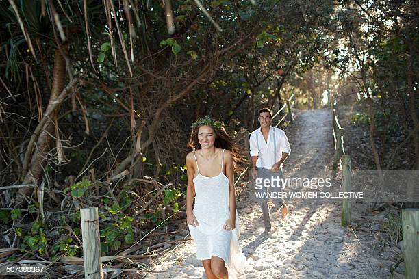 Young man chasing woman on path to beach
