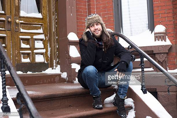 Young man chatting on smartphone on snow covered front door step