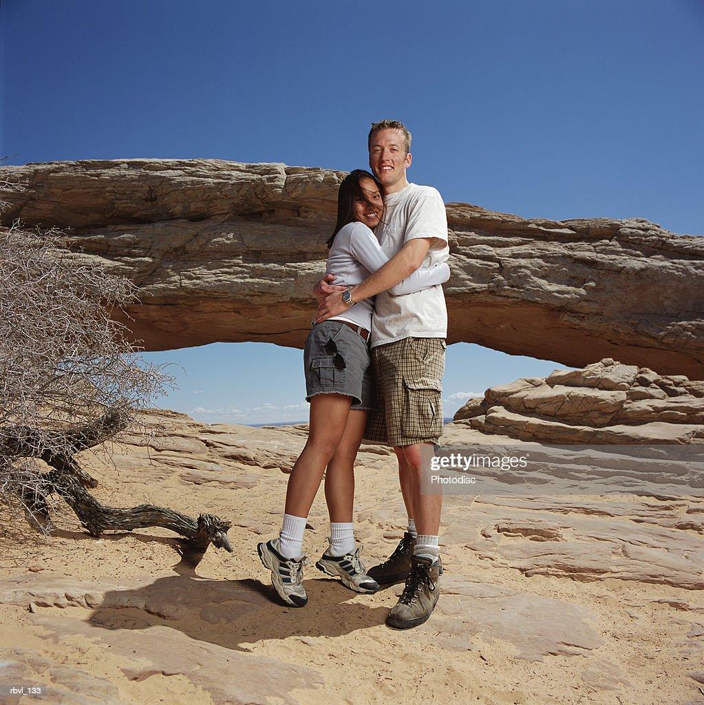 young man checkered shorts t-shirt hugs young woman in gray shorts white shirt at a natural arch : Bildbanksbilder