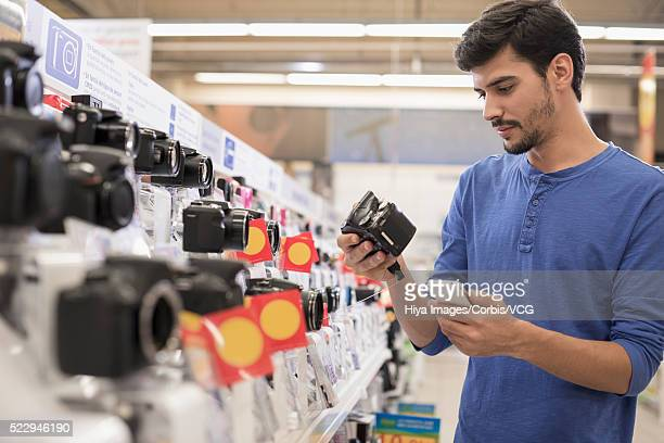 Young man checking camera in store