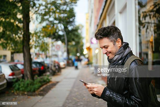 Young man checking cellphone in Berlin Germany