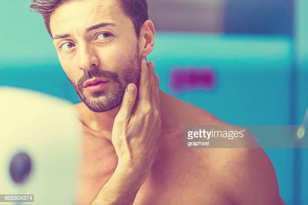Young Man Checking Face in Bathroom Mirror