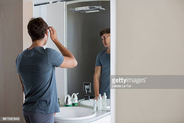 Young man checking his hair in mirror