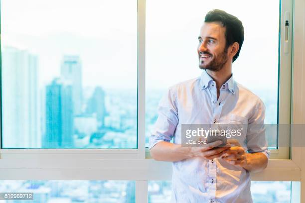 Young man checking his phone in his apartment