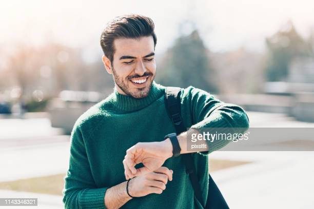 young man checking his smart watch - smart watch stock pictures, royalty-free photos & images