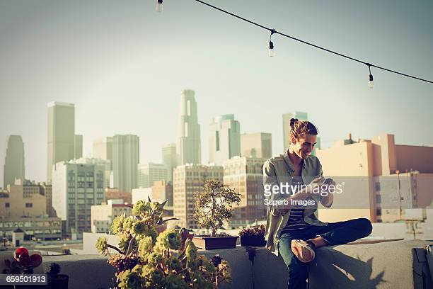 young man checking his smartphone on urban rooftop - los angeles città foto e immagini stock