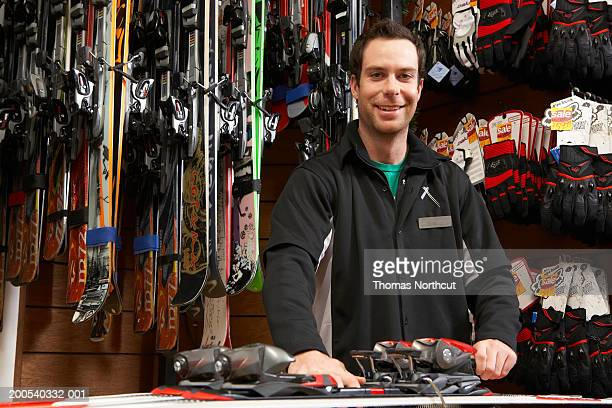 young man checking skis and bindings in sports shop, portrait - esqui equipamento esportivo - fotografias e filmes do acervo
