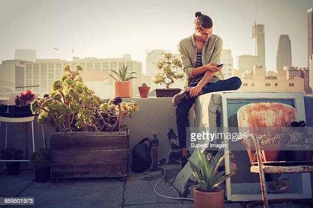 young man checking smartphone on urban rooftop - guardare verso il basso foto e immagini stock