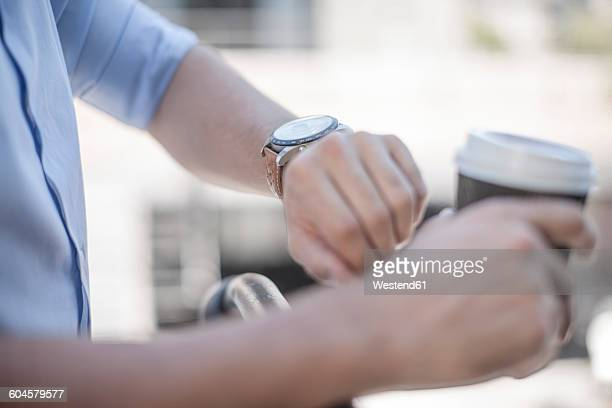 Young man checking time, looking at wrist watch