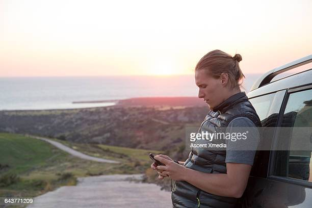 Young man checks phone by vehicle, above sea
