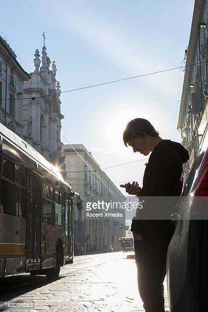 Young man checks text on urban street, bus passes