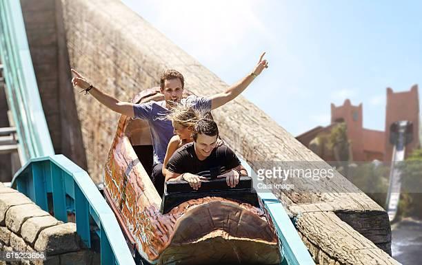 Young man cheering on log amusement park ride