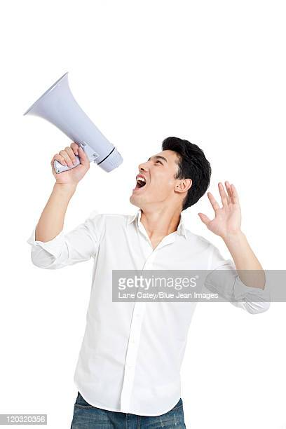 Young man cheering through a megaphone