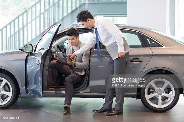 Young man choosing car in showroom