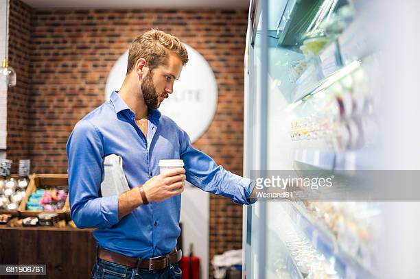 Young man choosing food from cooling shelf in a coffee shop