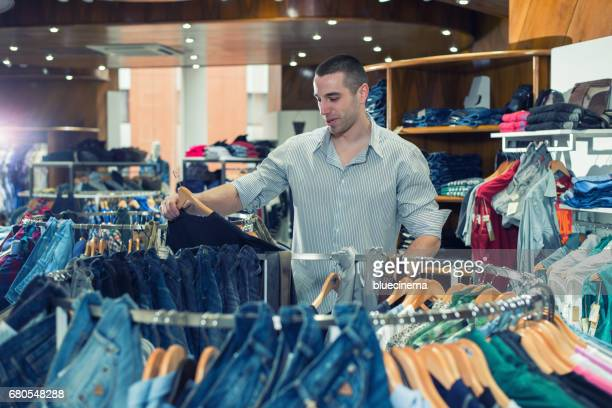 Young man choosing suit in clothes store