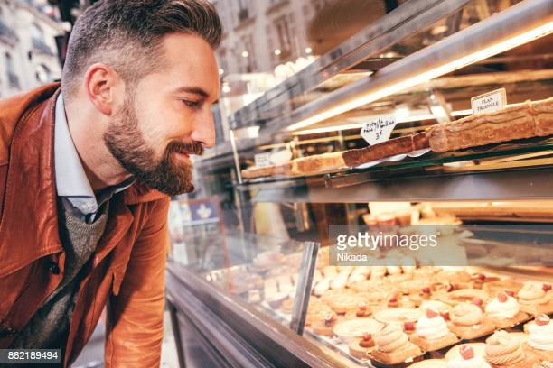 young man choosing sweets in paris, france - temptation stock pictures, royalty-free photos & images