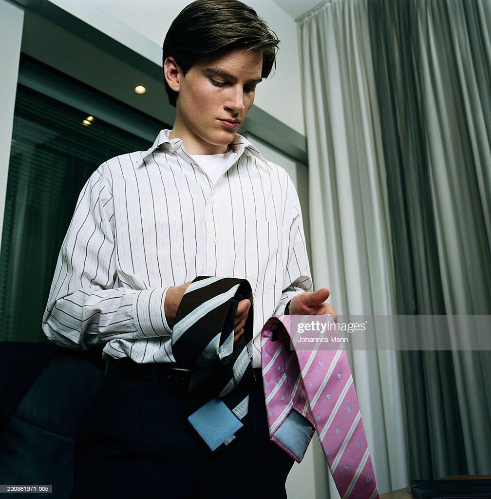 Young man choosing tie, low angle view : Stock Photo