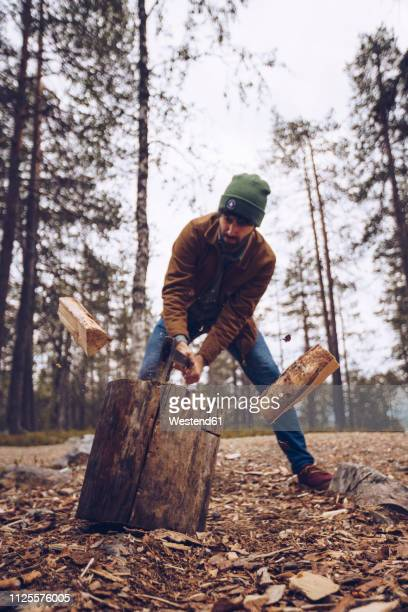young man chopping woog in the forest - chop stock pictures, royalty-free photos & images