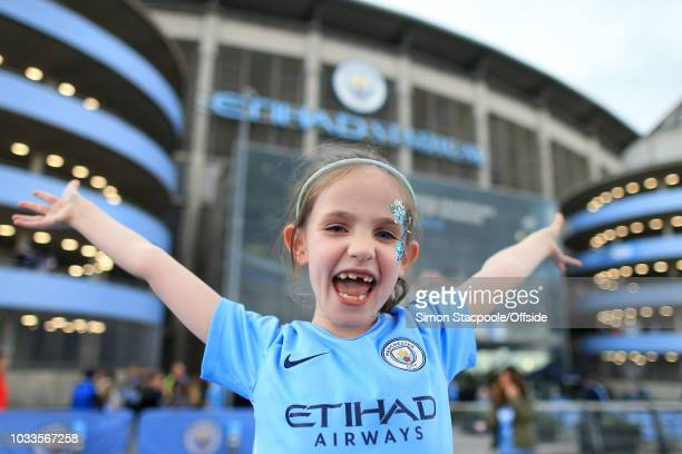 A young Man City fan cheers for her team ahead of the Premier League match between Manchester City and Fulham at the Etihad Stadium on September 15...