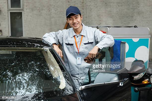 Young man cleaning car