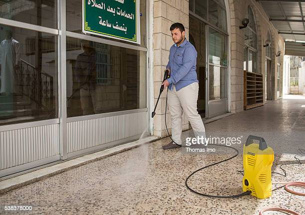 A young man cleans the floor in front of a mosque with a high pressure cleaner on April 08 2016 in Sweileh Jordan
