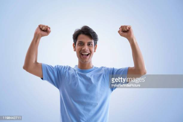 young man clenching fists and cheering - gesturing stock pictures, royalty-free photos & images
