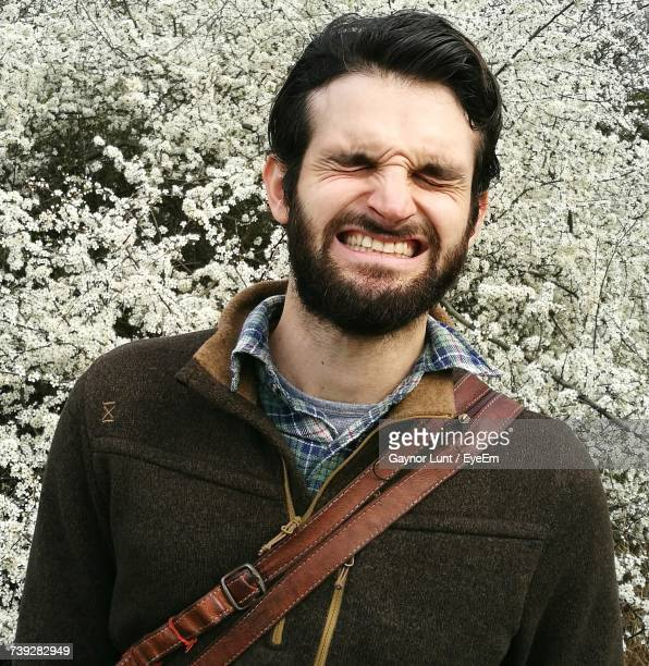 Young Man Clenching Teeth While Standing Cherry Blossom Trees At Park