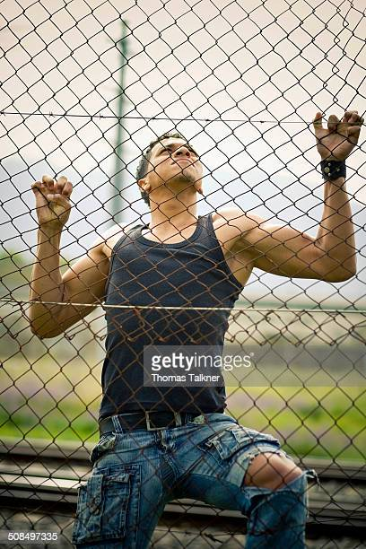 young man climbing a fence - prison escape stock pictures, royalty-free photos & images