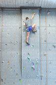 Young man climbing indoor rock wall