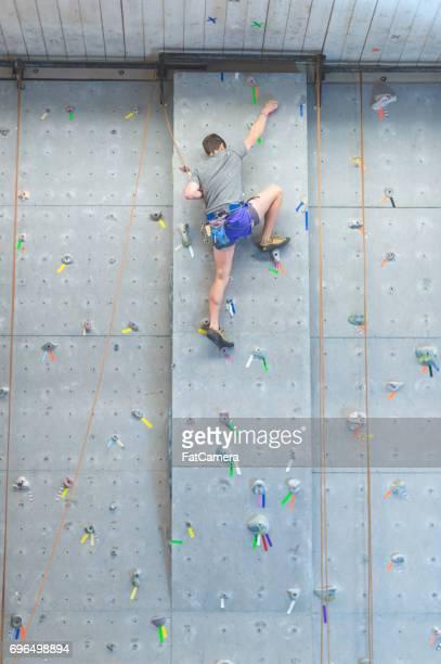 Junger Mann indoor Rock Kletterwand